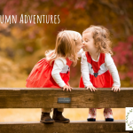 little girls kissing wearing fox pinafore dresses on a bench - Cotswold Baby Co