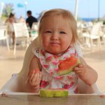 Picture of baby eating a watermelon - Cotswold Baby Co