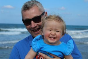 Daddy and daughter on holiday at the beach - Cotswold Baby Co