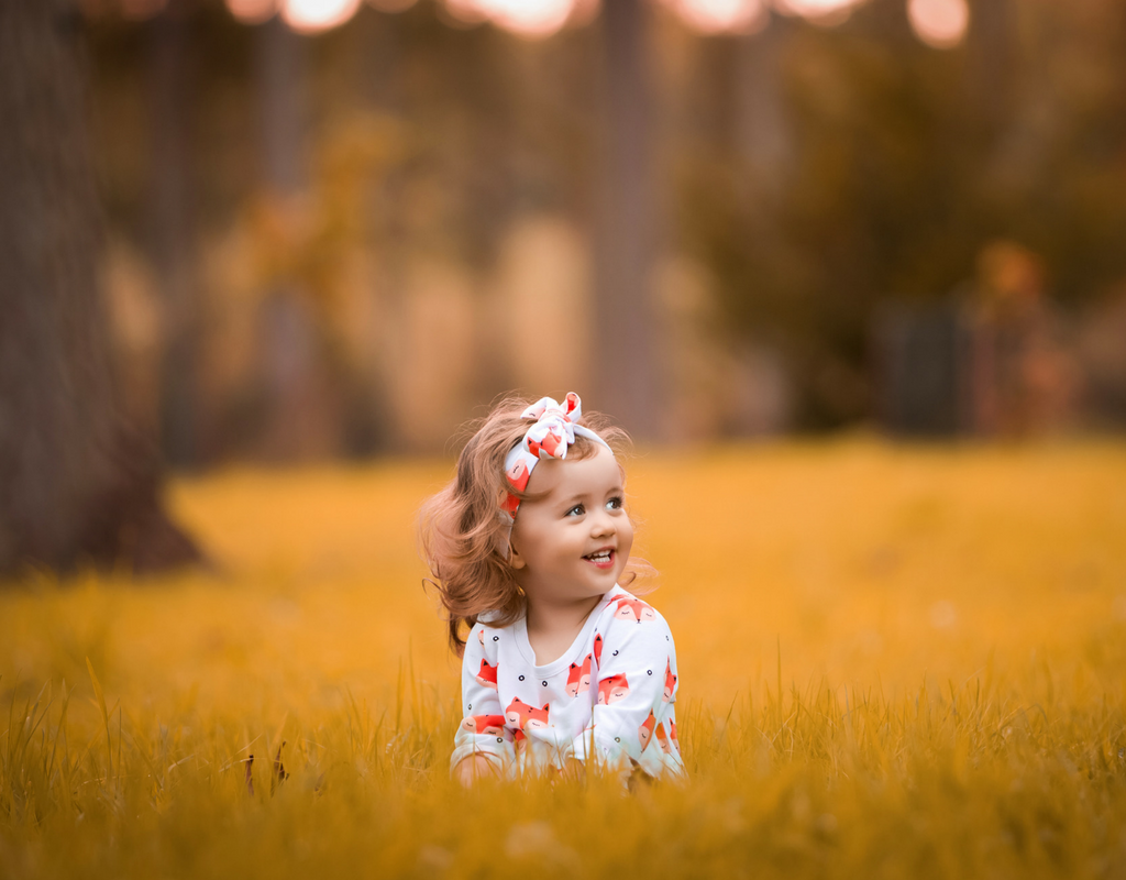 Little girl in the Autumn sunshine wearing a fox dress from Cotswold Baby Co