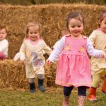 Little girls in farm themed dresses running - Cotswold Baby Co