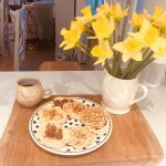 Plate with blueberry pancakes and a jug of daffodils