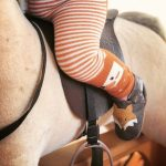 Baby on rocking horse wearing Inch Blue Leather Fox Shoes