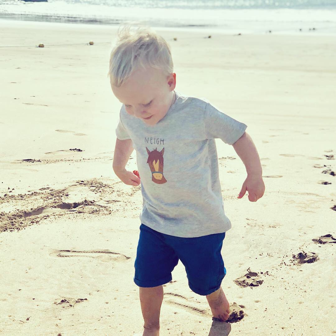 little boy at the beach wearing Cheeky Horse t-shirt by Cotswold Baby Co