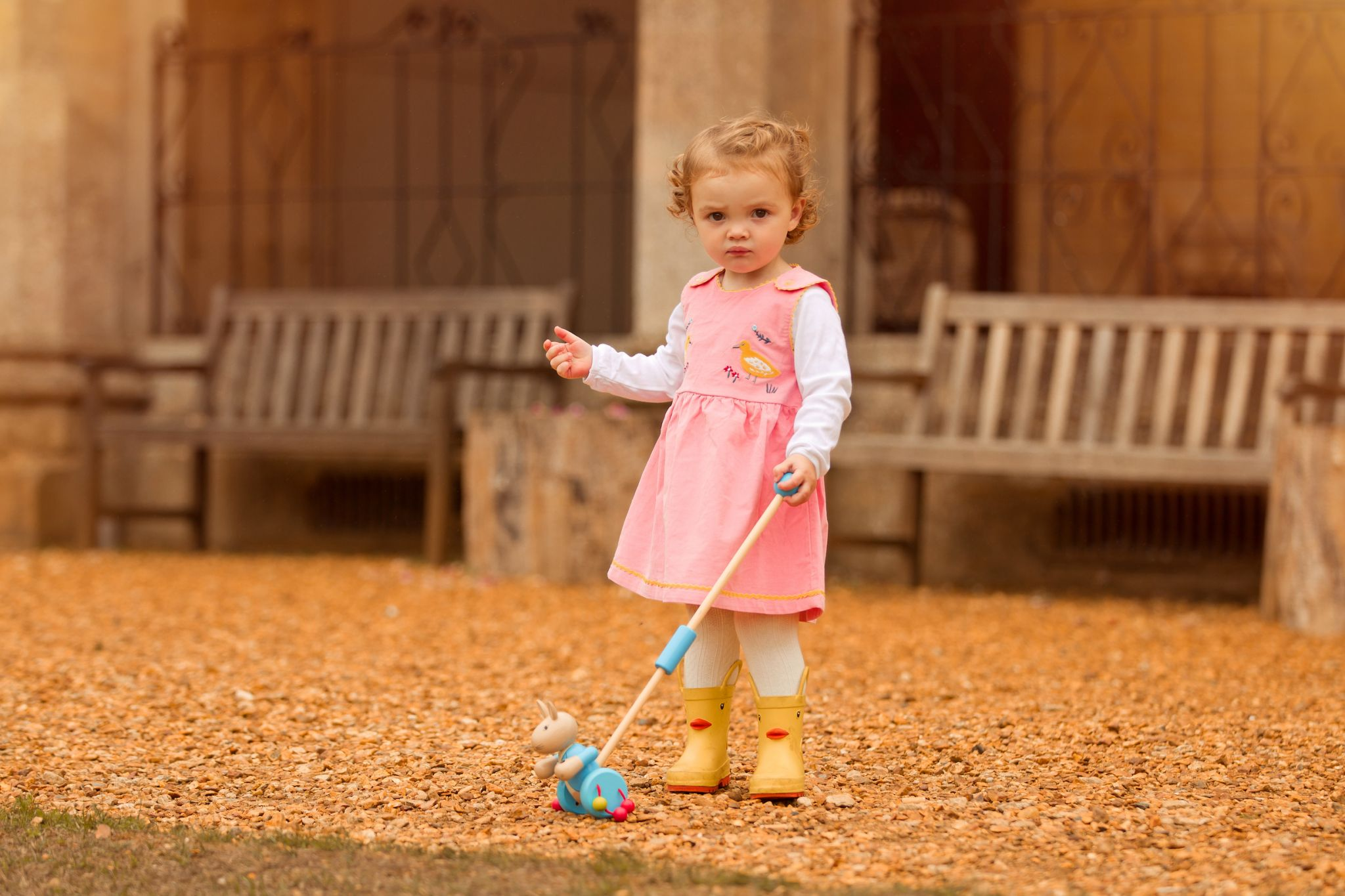 Little girl wearing pink cord duck dress by Cotswold Baby Co