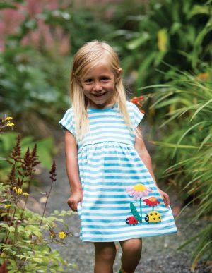 Little girl wearing Fliss Ladybird Applique Dress by Frugi