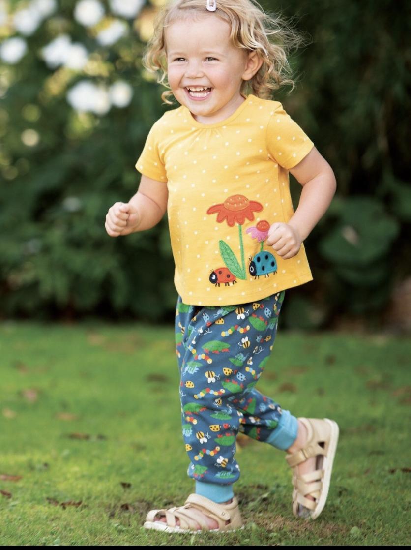 Little girl wearing yellow Ladybird Spotty top by Frugi